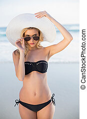 Stern blonde in elegant black bikini posing on a beautiful...