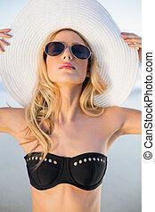 Peaceful sensual blonde in elegant black bikini posing on a...