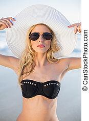 Serious sensual blonde in elegant black bikini posing on a...
