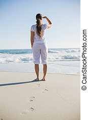 Rear view of gorgeous brunette on the beach looking away