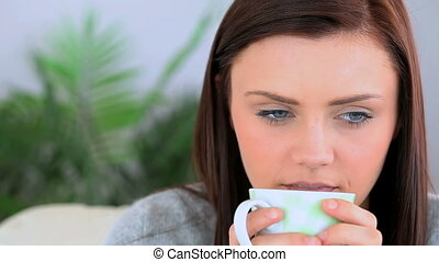 Brunette woman holding a cup of coffee and drinking
