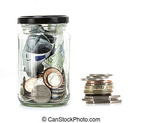 Glass jar with coins and notes from around the world on a...