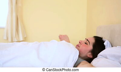 Woman waking up from bed in the bedroom