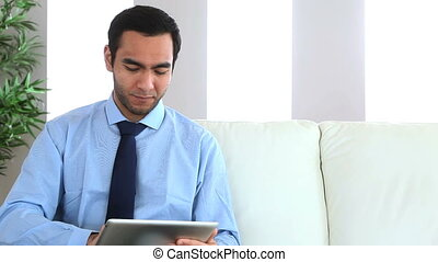 Businessman using his tablet sat on the couch