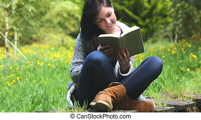 Woman sitting on grass reading a bo