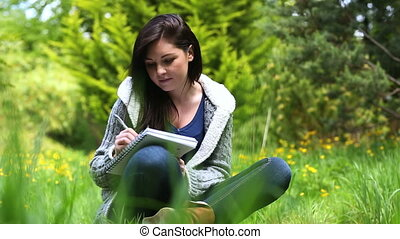 Woman sitting on grass writing on a - Pretty woman sitting...