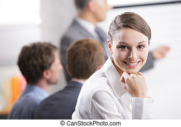 Meeting - Young businesswoman smiling in a meeting with her...