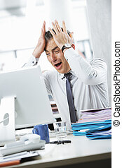 Frustrated Businessman sitting at desk in office -...