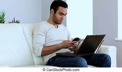 Man using his smartphone and his laptop sat on a couch