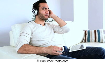 Man listening to music with his tablet computer sat on a...