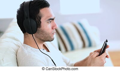 Man relaxing and listening to music with his phone sat on a...