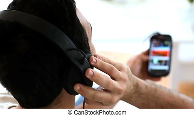Man moving his head while listening to music with his phone...