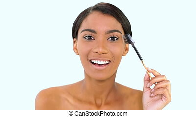 Woman brushing her eyebrows on white background