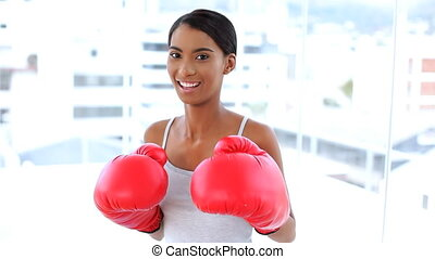 Woman fighting with boxing gloves - Cheerful woman fighting...
