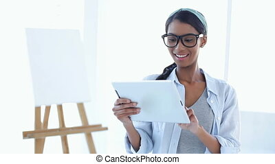 Artistic woman using a tablet pc on white background