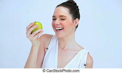 Woman holding a green apple against a white backgroud