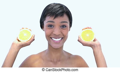 Beautiful woman holding slices of orange against a white...