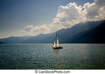 Sailing boat on a lake - Sailing boat on an alpine lake with...