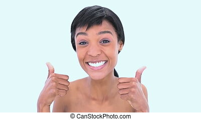 Woman giving thumbs up against a white background