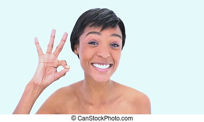 Woman making hand sign against a white background