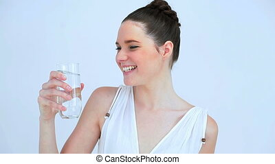 Smiling woman drinking a glass of water on white background