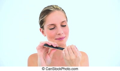 Blond woman filing her nails against a white background