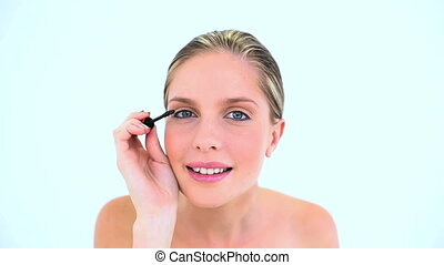 Blond woman making up her eye with mascara on white...