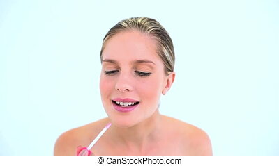 Smiling woman putting lipstick on her lips