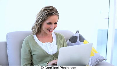 Smiling woman using laptop on couch and looking at camera
