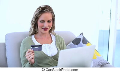 Delighted woman holding her credit card and using her laptop...