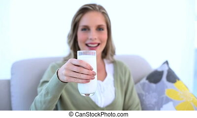 Woman showing her glass of milk to - Woman sat on couch...