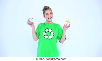 Attractive environmental activist holding two bottles on...