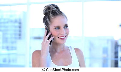 Attractive businesswoman talking on the phone in a bright...