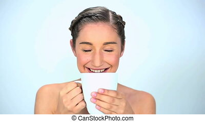 Young woman drinking her cup on white background