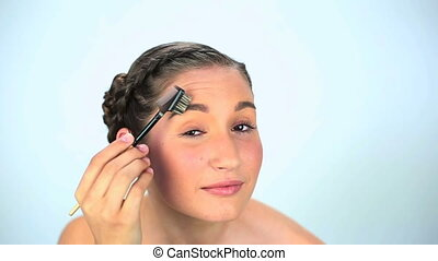 Young woman brushing her eyebrow on white background