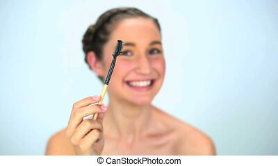 Smiling young woman brushing her eyebrow on white background