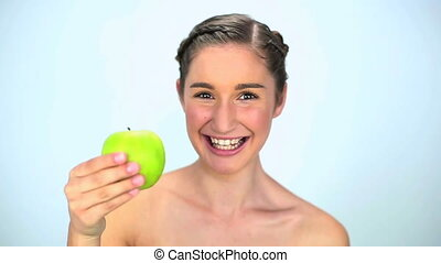 Young woman showing green apple
