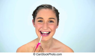 Smiling young woman applying lipgloss