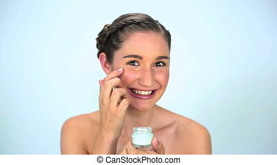 Smiling young woman applying cream on her face on white...