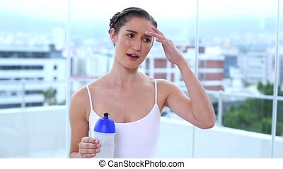 Smiling young woman drinking her flask in apartment