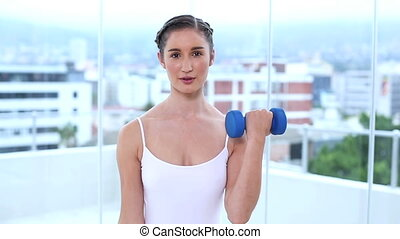Young woman holding dumbbells in apartment