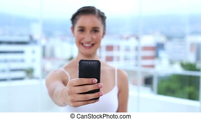 Young woman showing her mobile phone and texting a message...