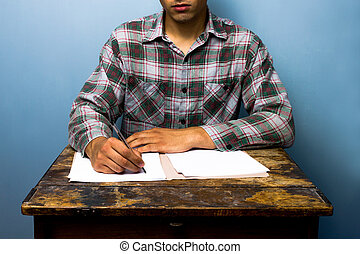 Young man writing at desk