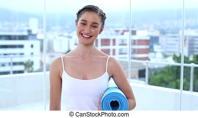 Young woman holding her fitness mat