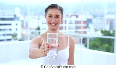 Happy young woman drinking water in apartment