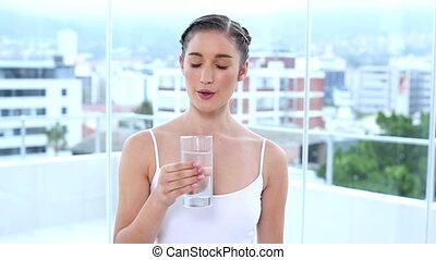 Cheerful young woman drinking water in apartment