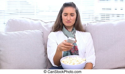 Brunette watching television and eating popcorn on sofa