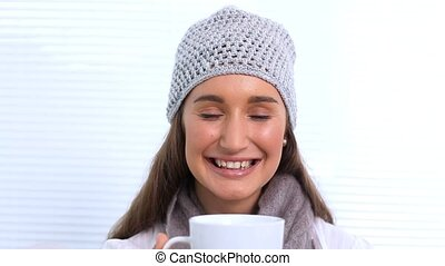 Young woman with hat and scarf smelling her cup at home