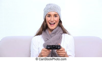 Brunette playing video games on sofa