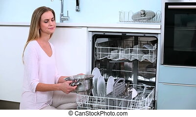 Unsmiling blonde woman put her dishes in dishwasher in...